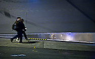 Two people are walking downhill past a rollup door with parallel lines in Seattle, WA, USA
