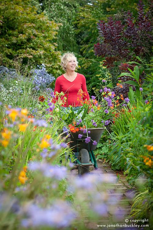 Carol Klein pushing wheelbarrow full of plants