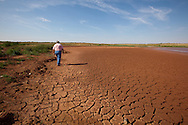 Lt.  Terry Chamness of the Big Spring Police Force walks on dry mud where water was in the J.B. Thomas Reservoir, On the Colorado River in West Texas is partially dried up and no longer usable. The Reservoir supplied Big Spring with much of its' water.  The Drought in Texas will have long term environmental and finical impact.