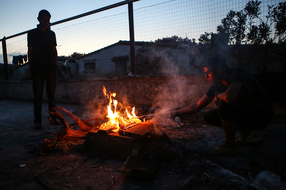 Migrants tend a fire where they will brew tea at the Hotel Captain Elia in Kos, Greece on June 30, 2015.