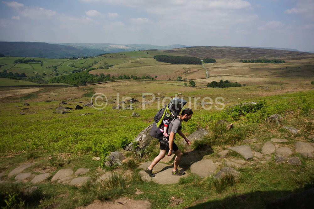 A father walks uphill carrying his child on an ancient stone footpath now suffering from erosion beneath Stanage Edge gritstone cliffs, Peak District National Park, Derbyshire. Beyond is a beautiful panorama of the Peak District National Park in England. Stanage Edge is the largest of the gritstone edges that overlook Hathersage in Derbyshire. Stanage Edge at approximately 4 miles in length and 458m at its highest point is the largest of the gritstone cliffs that overlook Hathersage, Derbyshire. The area is one of the most popular locations in the Peak District National Park for climbing and walking with hundreds of rock climbing routes to challenge all ranges of ability. Walkers are drawn to the area to enjoy the varied moorland scenery with stunning views across the surrounding countryside.