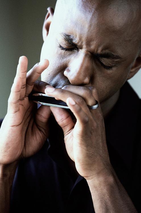 Portrait of man playing harmonica
