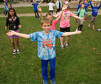 Kaden Dolloff and his 5th grade class do stretching exercises with Trish Tryon during the Elm Street School's Tiger Trek held at Leavitt Park on Friday morning.  (Karen Bobotas/for the Laconia Daily Sun)