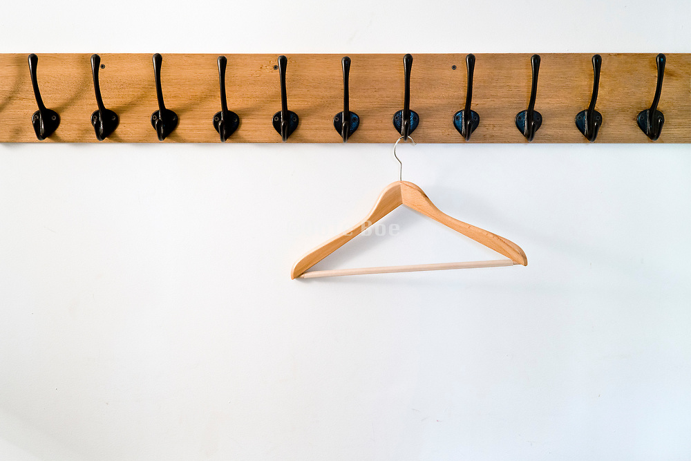 empty old style wall coat rack with wooden clothing hanger