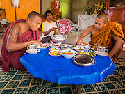 """01 MARCH 2014 - MAE SOT, TAK, THAILAND: A layperson fans Burmese Buddhist monks eating in a temple in a Burmese community in the forest a few kilometers north of Mae Sot. Mae Sot, on the Thai-Myanmer (Burma) border, has a very large population of Burmese migrants. Some are refugees who left Myanmar to escape civil unrest and political persecution, others are """"economic refugees"""" who came to Thailand looking for work and better opportunities.    PHOTO BY JACK KURTZ"""