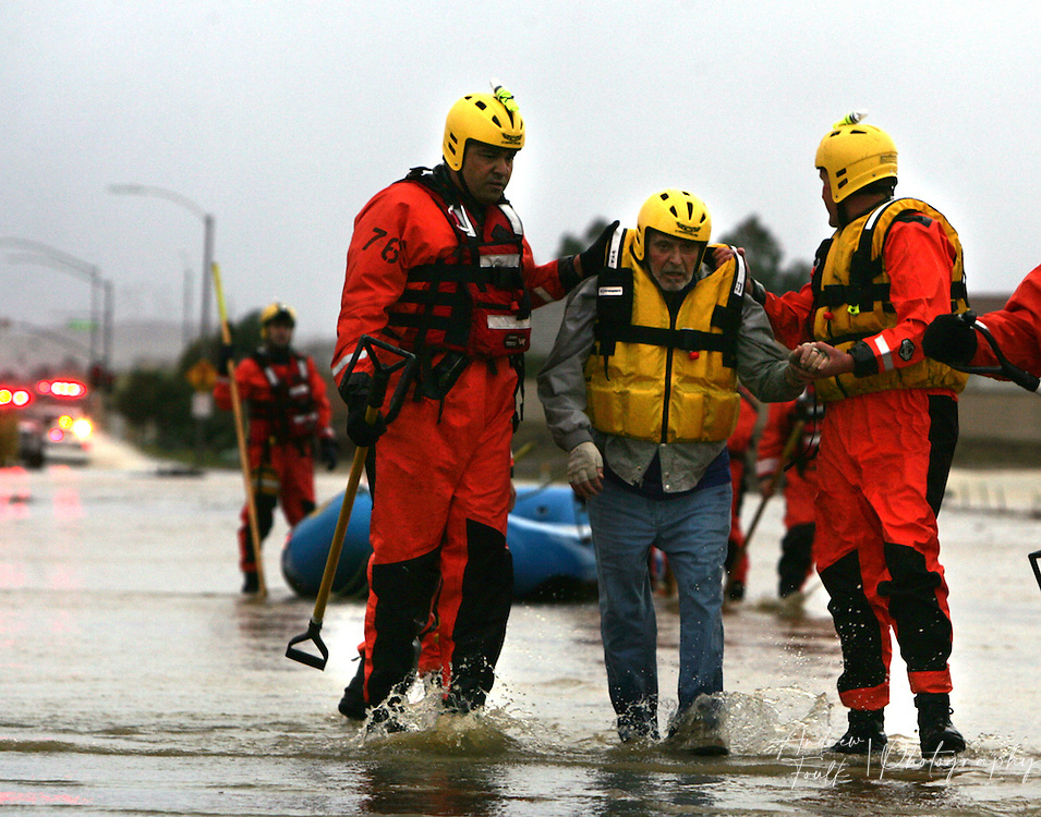 /Andrew Foulk/ For The Californian/ .Menifee Firefighters from station 76 walk a man from his SUV that was washed off the road after he drove down a flooded Newport Rd just East of La Ladera. The man had to be placed into a rescue boat do to concerns about the mans health and speed of the waters flow.