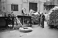 Two workers feeding jute into a machine at Tay Spinners mill in Dundee, Scotland. This factory was the last jute spinning mill in Europe when it closed for the final time in 1998. The city of Dundee had been famous throughout history for the three 'Js' - jute, jam and journalism.