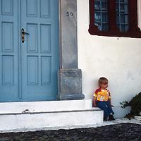 Europe, Mediterranean, Aegean, Greece, Greek Islands, Santorini, Thira. A young traveler rests on the step of a Santorini doorway.