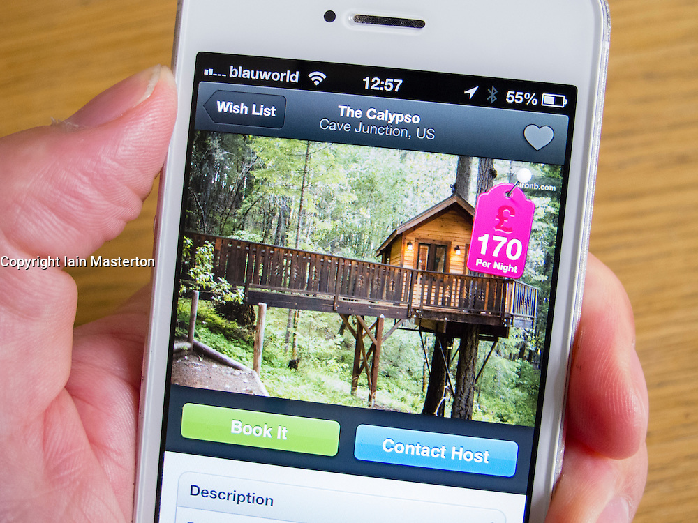 Using Airbnb app to book holiday accomodation in a treehouse on a white iPhone 5 smartphone