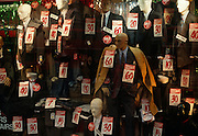 Filled with suits, jackets, trousers, and overcoats, the choices of mens' office worker clothes fill a shop front window belonging to Mr Byrite, a high-street clothes store chain in London England UK. Bargain sale prices for the items of clothing are all over the window display, offering discounts for £30, £40 or £60 and the mannequins used to wear these clothes either have bald-headed representations of men, or faceless white models wearing sun glasses. There is a sale of cheap items attracting young city men, far from traditional work attire, and more fashionable for the day.