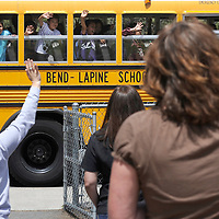 Faculty and staff wave goodbye to students as their busses pull away from Bear Creek Elementary following the last day of school on Thursday.