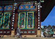 A buddhist monk walks by the Hall of the Great Hero or Daeung-jeon at Jogye-sa Buddhist Temple, Seoul, South Korea. Jogyesa is the main temple of the Jogye Order of Korean Buddhism, and has a important part in Seon Buddhism. Located in Gyeonji-dong, Jongno-gu within in the old city of Seoul. ..The greyness of the monk's clothes signify ashes and death.