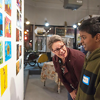 Jennifer Brown talks with 10 year-old artist Lakshan Sundaram after purchasing one of his paintings at the 8 x 10 x 20 Artist Challenge show opening Saturday night at Art123 Gallery in Gallup. The show features 20 local artists and runs through March 7.