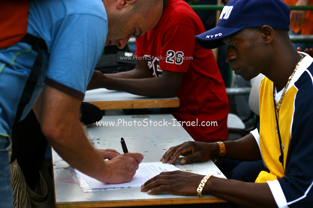 """An activist for the African workers in Israel union, sign people on a petition in attempt to prevent banishment of african refugees children and children of migrant workers.  Saturday, May 12, 2007. A black music festival """"Groove Refugee"""" took place in Tel Aviv, all income will serve the struggle to prevent those children deported from Israel."""
