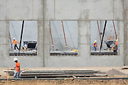 Construction workers clean up debris inside large pop-up buildings at the Dixon Landing Road exit of I-880, which is planned to be a shopping center named The Crossings @880, in Milpitas, California, on July 15, 2014. (Stan Olszewski/SOSKIphoto)
