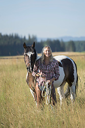 Mid adult woman standing with her horse on meadow and smiling, Bavaria, Germany