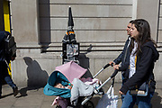 A family walk past Evening Standards with Prime Minister Theresa May on the front page, asking the nation to trust her and yesterdays snap election announcement, outside the Bank of England in the heart of the capitals financial district, on 19th April, in the City of London, England.