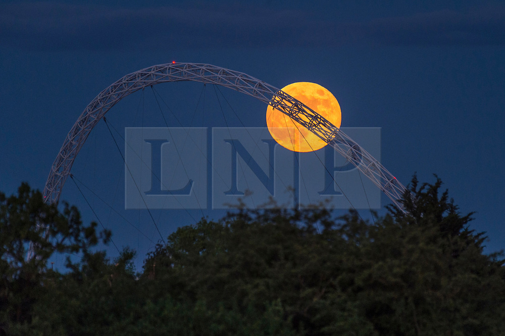 © Licensed to London News Pictures. 05/06/2020. LONDON, UK.  June's full moon, known as a Strawberry Moon, rises behind Wembley Stadium's arch in north west London.  June's full moon, according to The Old Farmer's Almanac, was the signal for Native American Algonquin tribes to harvest wild strawberries.  This month's full moon also coincides with a subtle penumbral eclipse, which occurs when the Earth casts a slight shadow over the Moon.  Photo credit: Stephen Chung/LNP