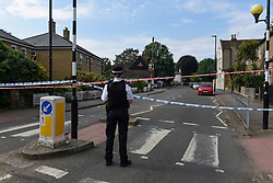© Licensed to London News Pictures. 25/08/2019. SOUTHALL, UK. A policewoman at the cordon of the scene adjacent to St Mary's Avenue near Southall in west London.  It is reported that a man in his 60s was stabbed outside The Plough pub on Tentelow Avenue in the early evening of 24 August and stumbled to nearby St Mary's Avenue to seek aid from a residence.  Police were called at 6.41pm, paramedics and air ambulance crews attended but the man passed away.  A man in his 30s has been arrested on suspicion of murder.  The investigation continues. Photo credit: Stephen Chung/LNP