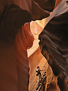 """Flash floods have eroded a slot of Navajo sandstone into a natural cathedral at Lower Antelope Canyon, in Antelope Canyon Navajo Tribal Park, near Page, Arizona, USA. (The older spelling """"Navaho"""" is no longer used by the Navajo, an American Indian group who call themselves Diné, or Dineh, """"The People."""")"""