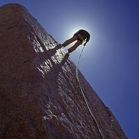 A rock climber rappels down a boulder in the Buttermilk Rocks