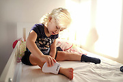 preschool girl is imitating her mother by playfully using a hair removal machine on her leg