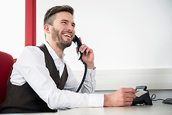 Man telephone conversation laughing office