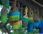 Colorful green and blue paint brushes hang from the porch of The Art Shack in Locke, California