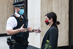 London, UK. 10 November, 2020. A Metropolitan Police officer prepares to arrest an environmental activist from Extinction Rebellion outside the Shell Centre on the 25th anniversary of the killings of the Ogoni Nine. The Ogoni Nine, leaders of the Movement for the Survival of the Ogoni People (MOSOP), were executed by the Nigerian government in 1995 after having led a series of peaceful marches involving an estimated 300,000 Ogoni people against the environmental degradation of the land and waters of Ogoniland by Shell and to demand both a share of oil revenue and greater political autonomy.