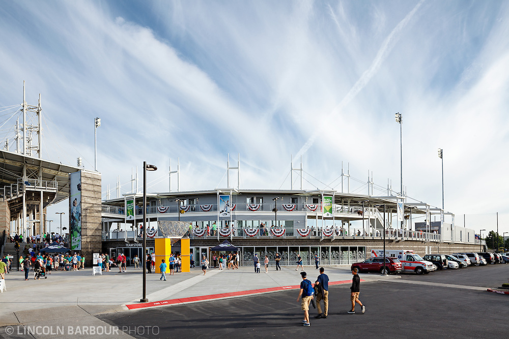 As seen from the outside, fans are filtering into a minor league baseball stadium on a beautiful day.