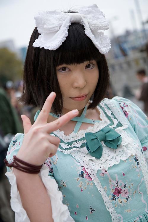 Asia, Japan, Tokyo, Harajuku area. Female teenager dressed as maid on Jingu Bridge.