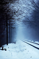 Train tracks fading into the distance on a foggy snow covered winter's day.