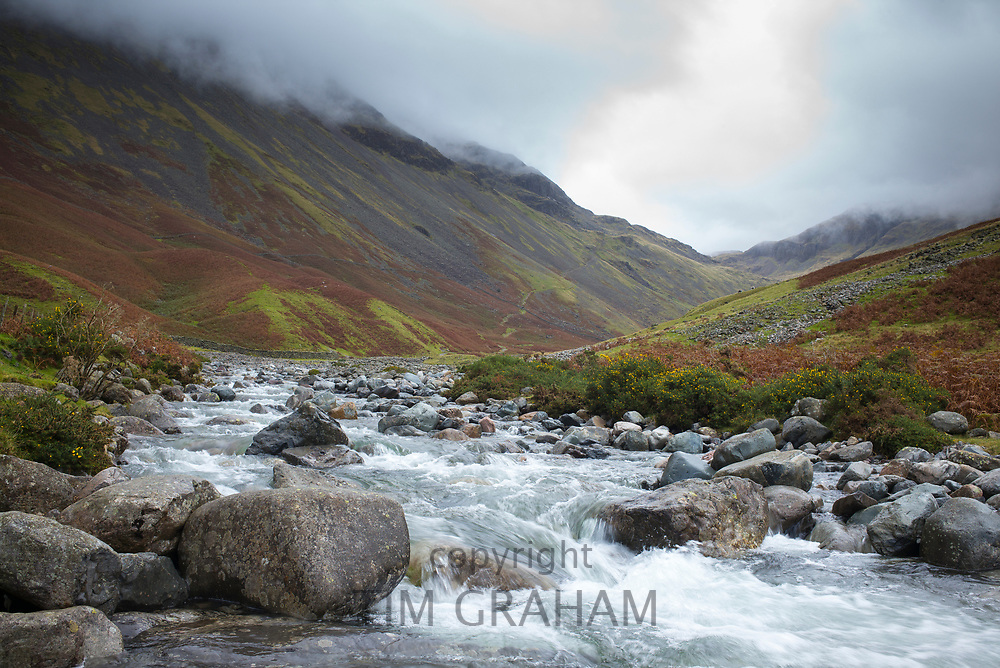 Low cloud over gushing mountain stream Lingmell Beck and lower slopes of Great Gable near popular tourist site Burnthwaite by Wasdale Head, the Lake District, UK
