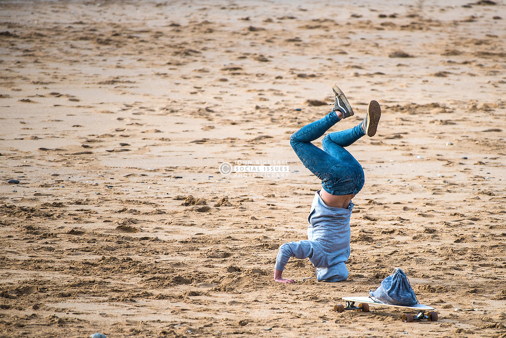 A teenage girl attempting to stand on her head on Fistral beach in Newquay, Cornwall.