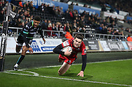 Blair Kinghorn of Edinburgh Rugby dives over for his teams 2nd try as Keelan Giles of the Ospreys tries to stop him. Guinness Pro12 rugby match, Ospreys v Edinburgh Rugby at the Liberty Stadium in Swansea, South Wales on Friday 2nd December 2016.<br /> pic by Andrew Orchard, Andrew Orchard sports photography.
