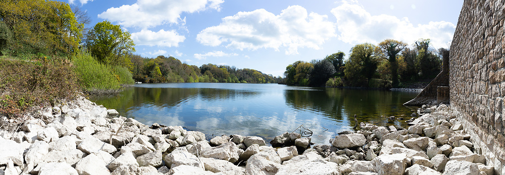 Panoramic view of the calm reflective water at Queen's Valley Reservoir in Jersey, Channel Islands