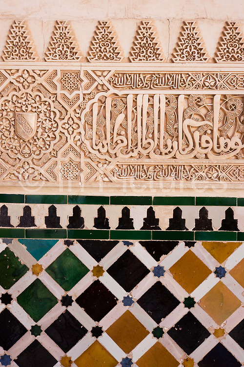 """Ornate architectural artwork on courtyard walls of Nasrid Palace. This is the Patio de los Arrayanes (Court of the Myrtles), also called the Patio de la Alberca (Court of the Blessing or Court of the Pond), from the Arabic birka, """"pool"""". There are galleries on the north and south sides; the southern gallery is 7 m (23 ft) high and supported by a marble colonnade. Underneath it, to the right, was the principal entrance, and over it are three windows with arches and miniature pillars. From this court, the walls of the Torre de Comares are seen rising over the roof to the north and reflected in the pond. The Alhambra's Moorish palaces were built for the last Muslim Emirs in Spain and its court, of the Nasrid dynasty."""