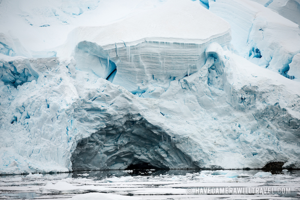 """A glacier of thick ice and snow gradually falls into the sea as it flows down the side of the mountains at the Lemaire Channel in Antarctica. The Lemaire Channel is sometimes referred to as """"Kodak Gap"""" in a nod to its famously scenic views."""