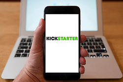 Using iPhone smartphone to display logo of Kickstarter website, a crowdfunding platform to fund creative startups