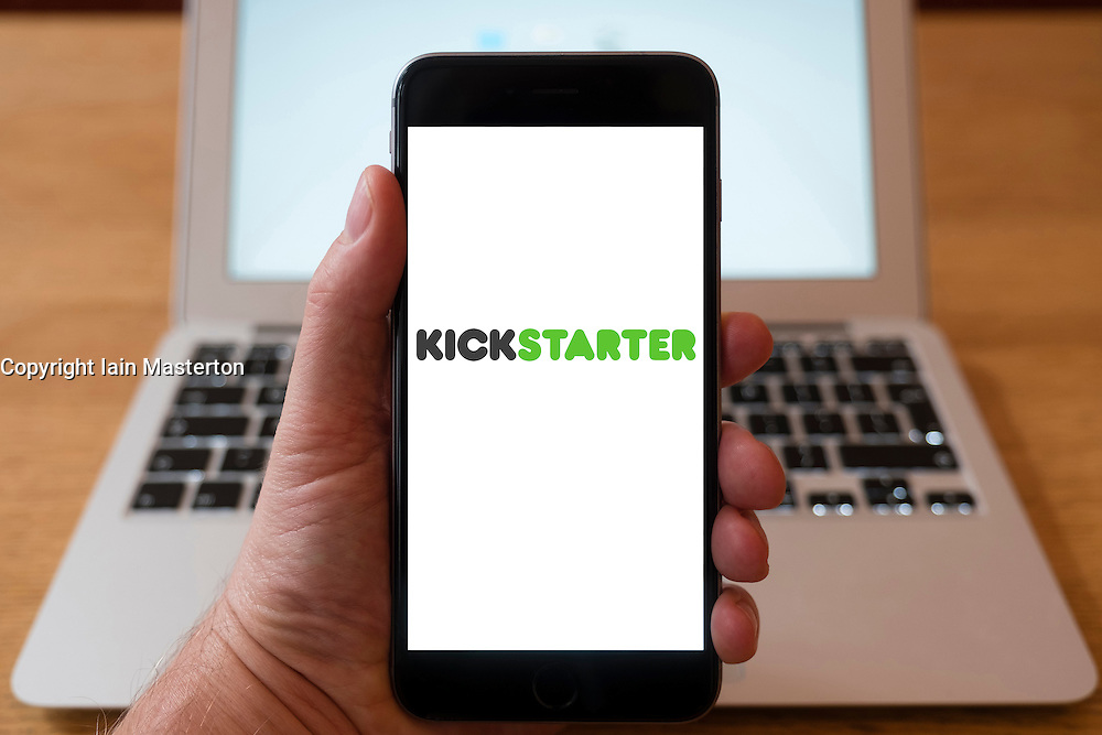 Using iPhone smartphone to display logo of Kickstarter website, a crowdfunding platform to fund creative startups