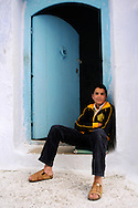 Morocco, Chefchaouen. Young boy sitting at the blue door in the medina.