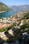 View from the medieval  hill fortifications above Kotor across roof tops and Kotor Bay - Montenegro . The old Mediterranean port of Kotor is surrounded by fortifications built during the Venetian period. It is located on the Bay of Kotor (Boka Kotorska), one of the most indented parts of the Adriatic Sea. Some have called it the southernmost fjord in Europe, but it is a ria, a submerged river canyon. .<br /> <br /> Visit our MONTENEGRO HISTORIC PLAXES PHOTO COLLECTIONS for more   photos  to download or buy as prints https://funkystock.photoshelter.com/gallery-collection/Pictures-Images-of-Montenegro-Photos-of-Montenegros-Historic-Landmark-Sites/C0000AG8SdQ.sYLU