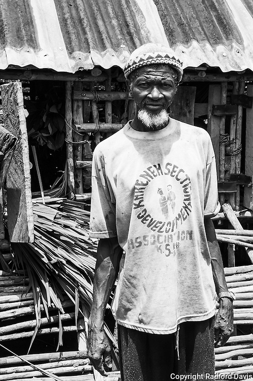 The Chief of Mabamboo village stands proudly in front of his goat houses. Goats should be confined, otherwise they roam and eat the crops of farmers, and then there is conflict within the community.