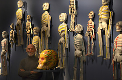 """© Licensed to London News Pictures. 14/11/2012. London, UK Collector Richard Harris poses with Death iconography from Mexico's Day of the Dead. . Press preview of """"Death: A Self -Portrait. The Richard harris Collection"""" at The Welcome Collection today 14th November 2012. The exhibition showcases 300 works from a unique collection devote to the iconography of death and mankind's attitude towards it. Photo credit : Stephen Simpson/LNP"""