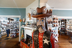 Wooden cowboy at Pendery's World of Chiles & Spices retail store with shoppers in background, Fort Worth, Texas USA.