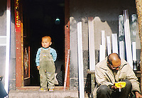 """China, Beijing, 2008. A boy surveys his """"hutong,"""" or traditional neighborhood. These low-slung communities are fast disappearing, as streets are widened, and concrete and steel construction replaces bricks in cities all over China.."""
