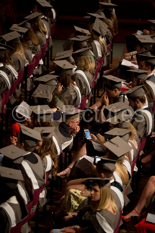 Young graduates wearing rented gowns and mortarboards look at social media in the central hall of their university, waiting for their graduation ceremony to start, on 13th July 2017, at the University of York, England.