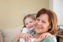 Portrait of grandmother and granddaughter sitting on couch in living room, smiling