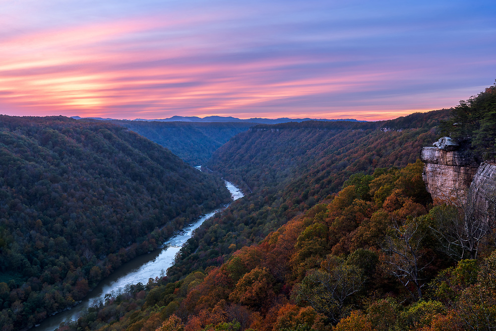 The sun sets in pastel purples over a New River Gorge painted in autumn colors from Beauty Mountain in West Virginia