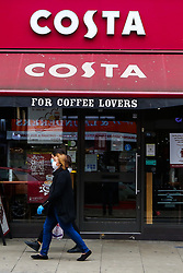 © Licensed to London News Pictures. 03/09/2020. London, UK. A woman wearing a face covering walks past Costa in north London as the coffee chain Costa Coffee announced that up to 1,650 roles are at risk of being cut due to the impact of the coronavirus pandemic.Photo credit: Dinendra Haria/LNP
